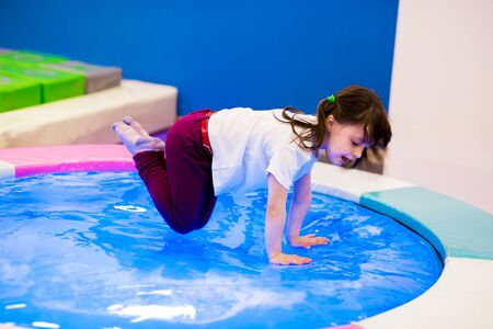 emotional girl preschooler with ponytails in a white T-shirt jumping on an inflatable water trampoline with backlight. entertainment in the games room.