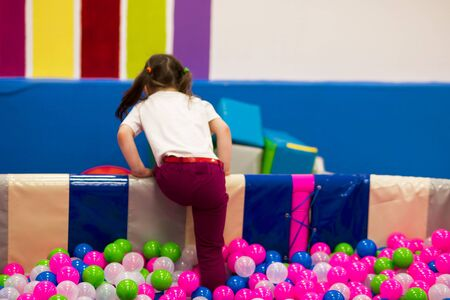 preschooler girl with ponytails in a white T-shirt crawls out from the pool with colorful balloons on the playground over the curb.