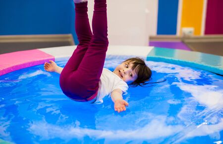 emotional little preschooler girl with ponytails in a white T-shirt lies on an inflatable water trampoline with backlight and legs raised up. playground entertainment. Banque d'images