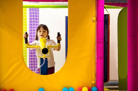 girl preschooler shoots from a yellow game blaster with foam soft balls. activities for children in the playground in the room.