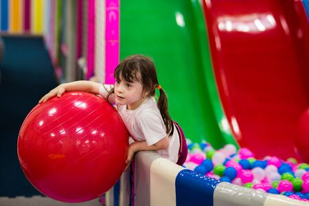 little preschooler girl in a white t-shirt plays with a big red fitball in the pool with colorful balloons on the playground.