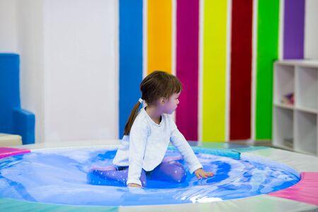 niña en edad preescolar con una chaqueta brillante juega con un trampolín de agua retroiluminado en una sala de juegos para niños.