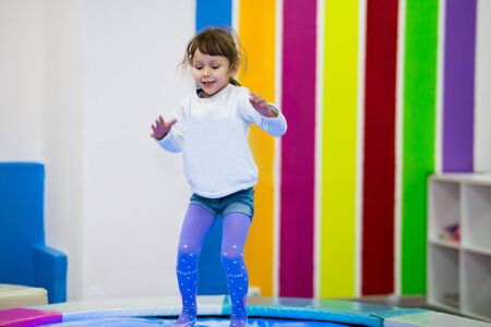 funny girl in a light jacket jumps on a trampoline with light in a children's playroom.