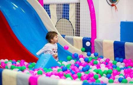 funny girl rolls down a plastic slide into a pool with balls at a children's playroom.