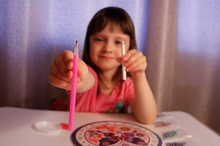 girl is engaged in diamond mosaic and chooses a pencil or stylus. handmade set for gluing rhinestones on a butterfly picture. A lesson for the development of fine motor skills for children and adults.