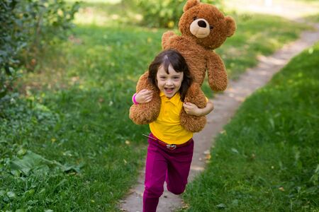 curly smiling girl in a yellow T-shirt holds a large brown teddy bear on her neck and runs along the path.