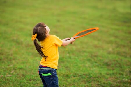 girl child 4-5 years old in a yellow T-shirt and jeans catches a ball with a racket on the nature. back view. Standard-Bild