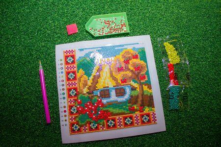 set of diamond mosaics for needlework in nature, on grass.