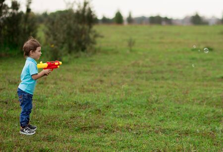 cute boy child 4-5 years old in a blue T-shirt and jeans plays a plastic toy water gun in nature.