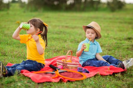 children - a boy in a blue T-shirt and wicker hat and a girl in a yellow T-shirt drink juice on a picnic.