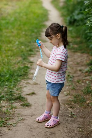 funny girl child in a white striped t-shirt and blue shorts inflates soap bubbles on the street