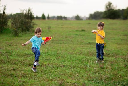 children - a boy in a blue T-shirt shoots with a water pistol, and a girl in a yellow blows out soap bubbles.