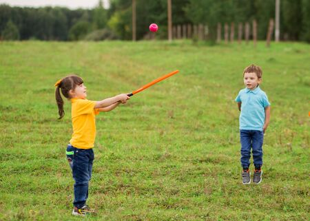 children - a boy in a blue T-shirt and a girl in yellow play tennis with rackets and a ball in nature together.