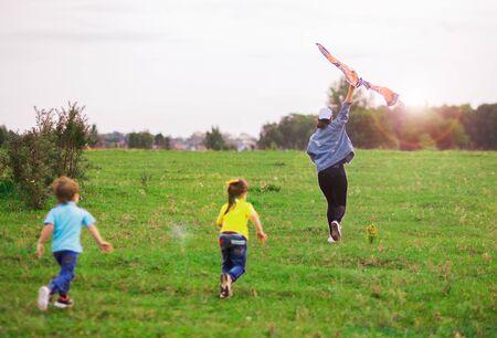 青いTシャツを着た男の子と黄色い女の子の2人の子供がカイトを遠くに走ります。