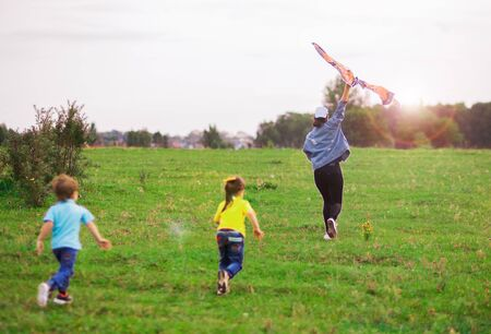 two children a boy in a blue T-shirt and a girl in yellow run for a kite into the distance.