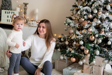 Beautiful mother and little daughter in white sweaters are hugging near the Christmas tree. family tender photo.