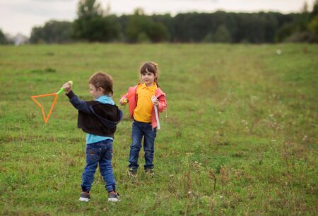 children - a boy in a black sweater and a girl in pink in nature blow gigantic soap bubbles.