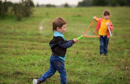 children - a boy in a black sweater and a girl in pink in nature blow gigantic soap bubbles. ball burst, aerosol.