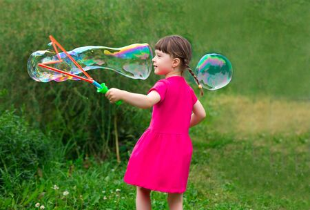 little kid girl with pigtails in a pink summer dress launches huge soap bubbles in the garden.