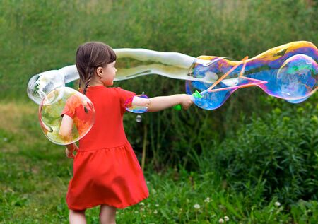 little kid girl with pigtails in a red summer dress launches huge soap bubbles in the garden. back view.