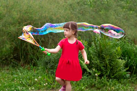 little kid girl with pigtails in a red summer dress launches huge soap bubbles in the garden. Foto de archivo