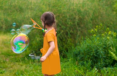 little kid girl with pigtails in a yellow summer dress launches huge soap bubbles in the garden.