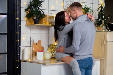 beautiful couple in love in gray clothes hugging and kissing on the kitchen table. Stylish Scandinavian style kitchen. emotions of people.