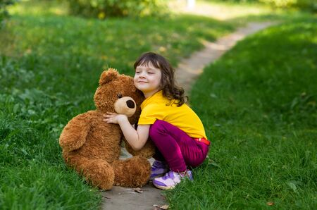beautiful curly girl in a yellow t-shirt squatted and hugs a big brown teddy teddy bear. around the greenery and the path.