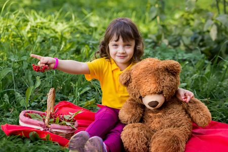 children's picnic in the autumn on the grass. happy girl with a teddy bear hug, eat rowan and look into the distance