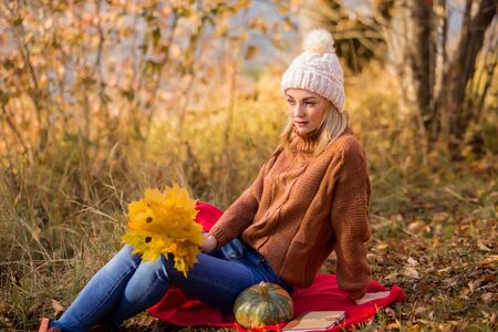 female portrait. beautiful blonde in a white knitted hat, brown sweater sits on a plaid in the park, holds a bouquet of leaves, looks into the distance. horizontal photo.