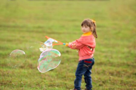 cute girl child 4-5 years old in a pink sweater, yellow T-shirt and jeans blows giant soap bubbles in nature.