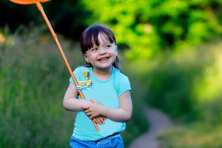 funny girl child 3 years old with a bang in a blue t-shirt holds a butterfly net and smiles.