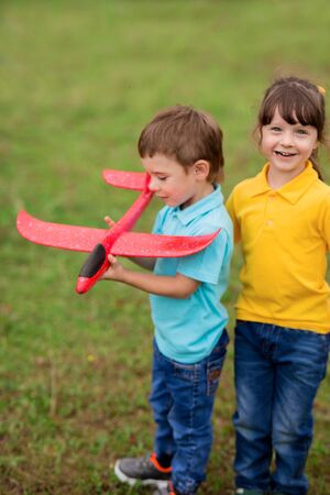 children - a boy in a blue T-shirt and a girl in yellow play a foam plastic toy red plane in nature Foto de archivo
