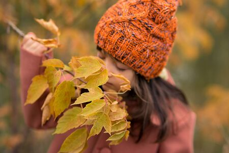 leaves in focus, the child in blur. girl preschooler in a brown coat and orange hat holds a branch, examines it and sniffs. large portrait of a kid. horizontal photo autumn
