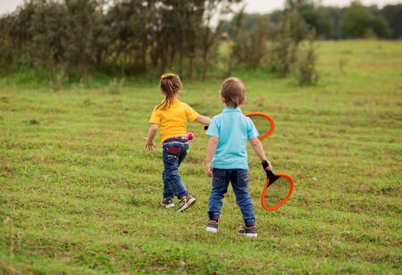 children - a boy in a blue T-shirt and a girl in yellow play tennis with rackets and a ball on nature Foto de archivo