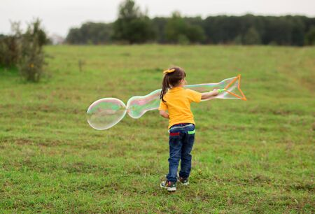 cute girl child 4-5 years old in a yellow T-shirt and jeans blows big soap bubbles in nature.