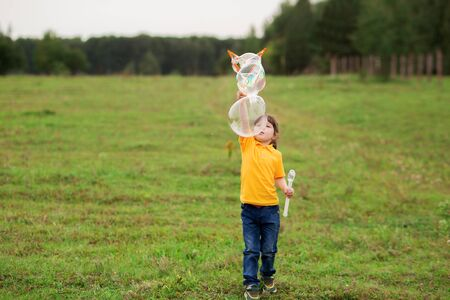 cute girl child 4-5 years old in a yellow T-shirt and jeans blows big soap bubbles in nature