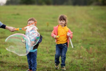 children - a boy in a black sweater and a girl in pink in nature blow gigantic soap bubbles Foto de archivo