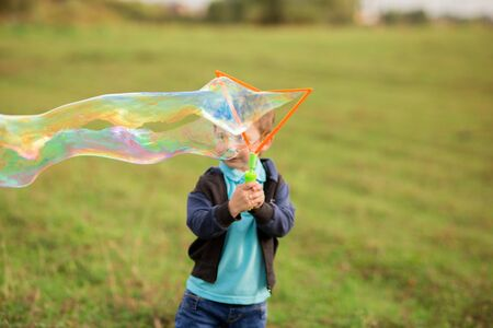 cute boy child 4-5 years old in a black sweater, blue t-shirt and jeans blows giant soap bubbles in nature.