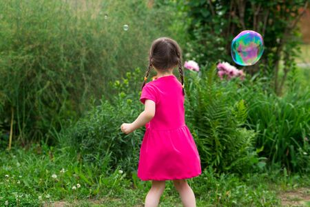 little kid girl with pigtails in a pink summer dress launches huge soap bubbles in the garden. back view.