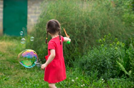 little kid girl with pigtails in a red summer dress launches huge soap bubbles in the garden.