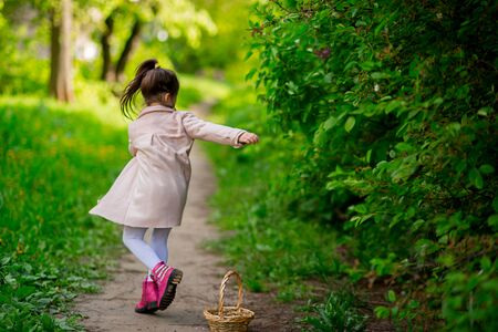 Cute kid girl in a pink coat and boots swirls around herself. ponytail hairstyle flies to the side. around nature.