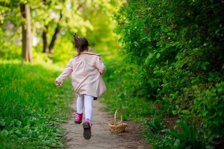 back view. cheerful child girl with a tail in a pink coat and boots runs forward along the path. around beautiful bushes, grass.
