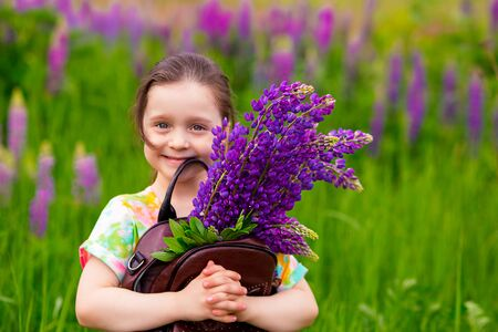 kid girl holding a brown backpack filled with purple flowers lupins.