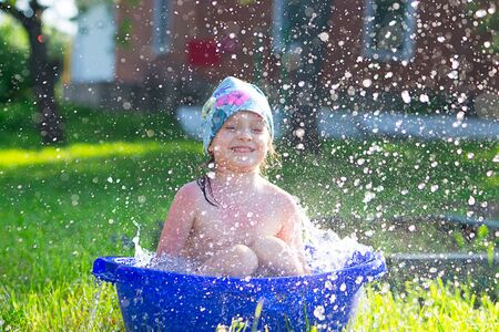 funny smiling kid girl bathes and squirts in water in a small basin in nature.