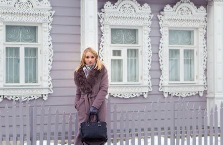 blonde girl in a gray coat with fur looks into the distance against the background of an old wooden house with platbands. 版權商用圖片