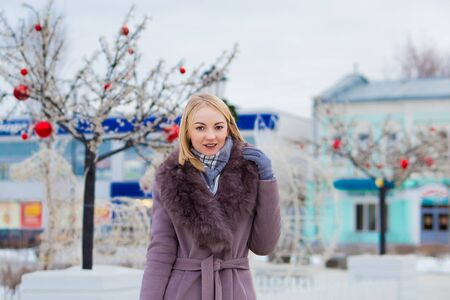 beautiful blonde in a brown coat with fur smiling. street in the city is decorated for Christmas. 版權商用圖片