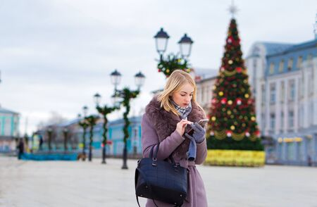 beautiful stranger in a brown coat looks at a mobile phone in the city, against the background of a Christmas tree and lights.