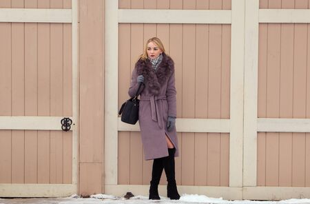 blonde girl in a brown coat with fur, high boots posing on a background of an old wooden door
