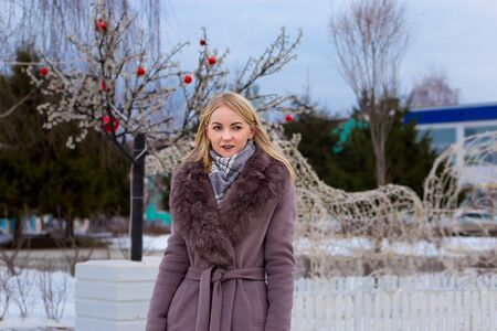 stranger blonde in a brown coat smiles, walks along a city street decorated for Christmas. 版權商用圖片